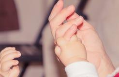 Mano recién nacida del bebé que sostiene el finger adulto, concepto de maternidad Fotografía de archivo libre de regalías