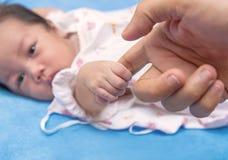 Mano recién nacida linda del bebé que sostiene el finger de la madre Imagen de archivo libre de regalías