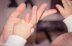 Mano recién nacida que juega con el finger adulto, concepto de maternidad del bebé Imagen de archivo