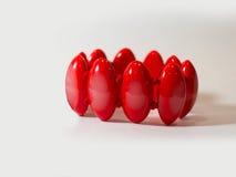 Mano roja de la pulsera en un fondo blanco Foto de archivo