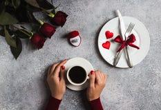 Mano romántica de la mujer del ajuste de la tabla de cena del día de tarjetas del día de San Valentín que sostiene la taza de caf Imágenes de archivo libres de regalías