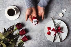 Mano romántica del hombre del ajuste de la tabla de cena del día de tarjetas del día de San Valentín que lleva a cabo el anillo d Imagenes de archivo