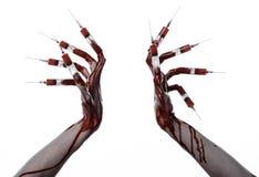 Mano sangrienta con la jeringuilla en los fingeres, jeringuillas de los dedos del pie, jeringuillas de la mano, mano sangrienta h Fotos de archivo