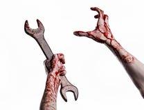 Mano sangrienta que sostiene una llave grande, llave sangrienta, llave grande, tema sangriento, tema de Halloween, mecánico loco, Imágenes de archivo libres de regalías