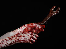 Mano sangrienta que sostiene una llave grande, llave sangrienta, llave grande, tema sangriento, tema de Halloween, mecánico loco, Fotografía de archivo libre de regalías