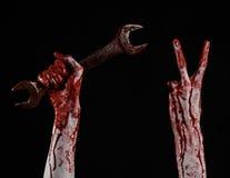Mano sangrienta que sostiene una llave grande, llave sangrienta, llave grande, tema sangriento, tema de Halloween, mecánico loco, Imagen de archivo libre de regalías
