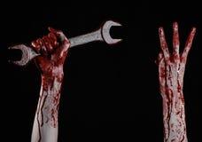Mano sangrienta que sostiene una llave grande, llave sangrienta, llave grande, tema sangriento, tema de Halloween, mecánico loco, Fotografía de archivo
