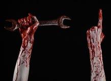 Mano sangrienta que sostiene una llave grande, llave sangrienta, llave grande, tema sangriento, tema de Halloween, mecánico loco, Foto de archivo libre de regalías