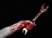 Mano sangrienta que sostiene una llave grande, llave sangrienta, llave grande, tema sangriento, tema de Halloween, mecánico loco, Fotos de archivo libres de regalías