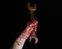 Mano sangrienta que sostiene una llave grande, llave sangrienta, llave grande, tema sangriento, tema de Halloween, mecánico loco, Foto de archivo