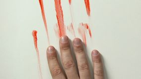 Mano sanguinosa che fa scorrere giù la parete, la morte della vittima, l'uccisione di contratto o il primo piano di omicidio archivi video