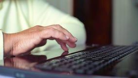 Mano senior della donna anziana del primo piano su Internet praticante il surfing della tastiera del computer portatile a casa co video d archivio