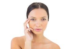 Mano seria della tenuta della donna sul suo fronte che esamina macchina fotografica Immagini Stock