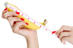 Mano sexy della donna con i chiodi rossi che tengono e che misurano banana Fotografia Stock