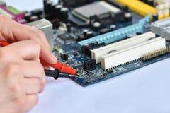 Mano sobre tablero con los componentes Reparación de ordenadores y de tecnologías modernas foto de archivo