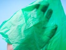 Mano sotto il film verde del sacchetto di plastica Fotografia Stock
