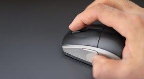 Mano su un topo del computer con lo spazio della copia Immagine Stock