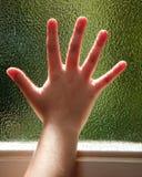 Mano su una finestra di vetro fotografia stock libera da diritti