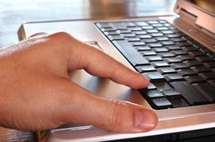 Mano sul computer portatile Fotografia Stock
