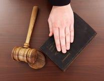 Mano sul libro e sul martelletto di legge immagine stock libera da diritti