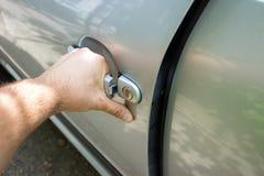 Mano sulla maniglia Primo piano della mano dell'uomo che apre una porta di automobile Fotografia Stock