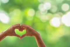 Mano sulla sfuocatura in forma di cuore del fondo del bokeh, stile naturale dell'annata di toni Mostri il mondo che amate, l'amor Fotografie Stock Libere da Diritti