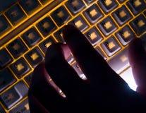 Mano sulla tastiera di illuminazione immagini stock libere da diritti