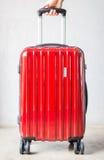 Mano sulla valigia di viaggio rossa Fotografia Stock Libera da Diritti