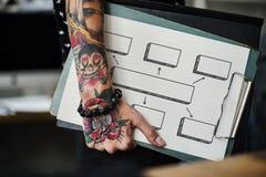 Mano tatuada que sostiene un tablero fotografía de archivo libre de regalías