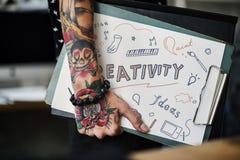 Mano tatuada que sostiene un tablero de la creatividad fotografía de archivo