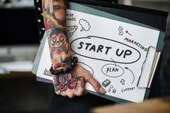 Mano tatuada que sostiene un tablero de lanzamiento fotos de archivo