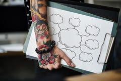 Mano tatuada que sostiene un tablero de papel en blanco imagen de archivo libre de regalías