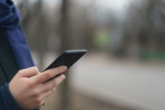 Mano teenager femminile facendo uso del outddor dello smartphone sulla via vuota della città nella mattina di primavera Fotografia Stock Libera da Diritti