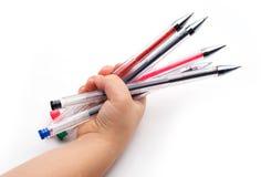 Mano tenendo le penne colorate Fotografie Stock Libere da Diritti