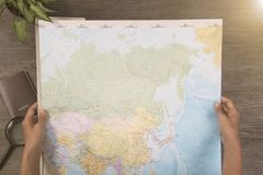 Mano turística que sostiene el mapa del mundo para las vacaciones de planificación Fotografía de archivo libre de regalías