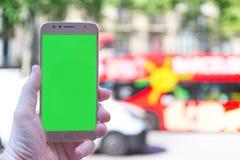 Mano turística que sostiene un smartphone en Barcelona que toma y que tira algunas fotos en España Pantalla dominante de la croma imagen de archivo libre de regalías