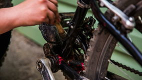 Mano umana che lava bicicletta professionale con la spazzola video d archivio