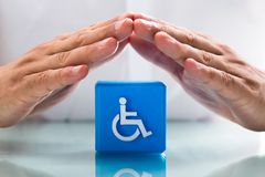 Mano umana che protegge blocco cubico con l'icona di handicap immagini stock