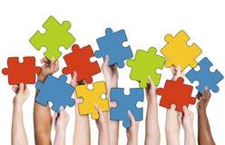 Mano umana che tiene i pezzi Colourful del puzzle fotografia stock libera da diritti