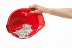 Mano umana che tiene un casco rosso con soldi Fotografie Stock