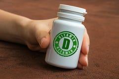 Mano umana che tiene una bottiglia delle pillole con la vitamina D Fotografie Stock Libere da Diritti