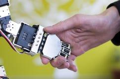 Mano umana che tiene una mano del robot con una stretta di mano Fotografie Stock
