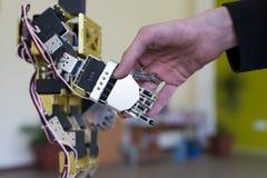 Mano umana che tiene una mano del robot con una stretta di mano Fotografia Stock