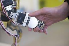 Mano umana che tiene una mano del robot con una stretta di mano Immagini Stock Libere da Diritti