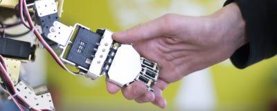 Mano umana che tiene una mano del robot con una stretta di mano Immagine Stock