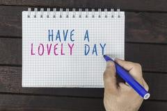 Mano umana con il testo di scrittura dell'indicatore sul blocco note: Abbia un giorno adorabile immagini stock libere da diritti