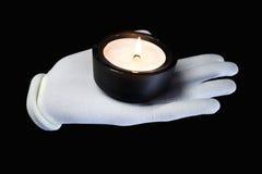Mano in un guanto bianco con le candele burning Fotografie Stock Libere da Diritti