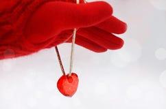 Mano in un guanto rosso e cuore rosso su un fondo bianco immagine fotografia stock