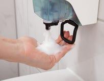 Mano usando dispensador del jabón Foto de archivo