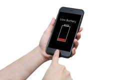 Mano usando el teléfono elegante con la advertencia baja de la muestra de la batería en el disp Fotografía de archivo